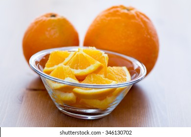 Couple of orange slices in a white bowl, on a wooden surface with whole oranges in the background