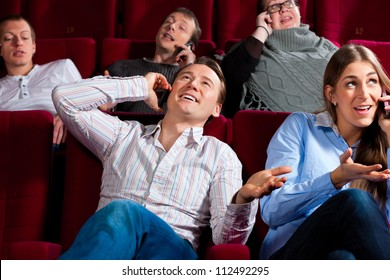 Couple and other people, probably friends, in cinema watching a movie, everybody is making a phone call, it seems to be a boring movie