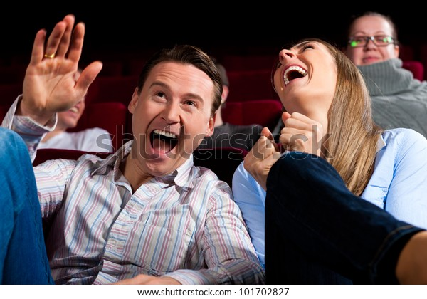 Couple and other people, probably friends, in cinema watching a movie, it seems to be a funny movie