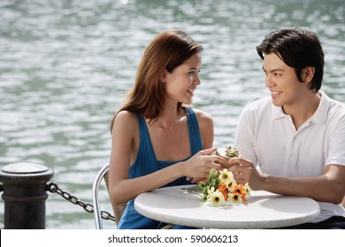 Couple at outdoor cafe, man giving woman a gift