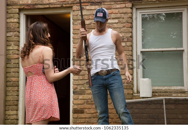 Couple outdoors, he is holding a shotgun