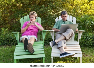 Couple outdoors relaxing...each busy with his own technology (laptop and MP3). Some motion blur.