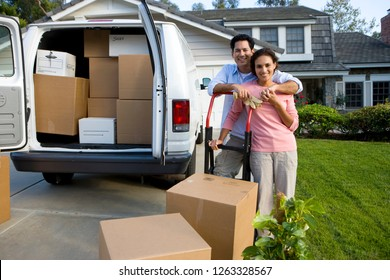 Couple outdoors with van moving boxes into new home at camera