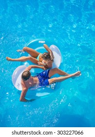 Couple Outside Relaxing In Swimming Pool in the summertime
