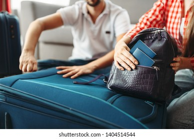 Couple packing their suitcases and take documents