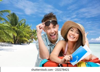 Couple packt den Koffer mit Kleidung für Flitterwochen, tropischer Strandhintergrund. Konzept für romantische Ferien und schöne Flitterwochen