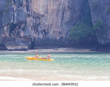 Couple paddle a kayak on the sea.
