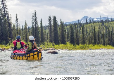 Couple paddling the whitewater of the Nahanni River in the Northwest Territories.