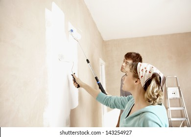 Couple painting wall together with paint rollers