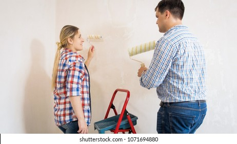 Couple painting walls at home with paint rollers