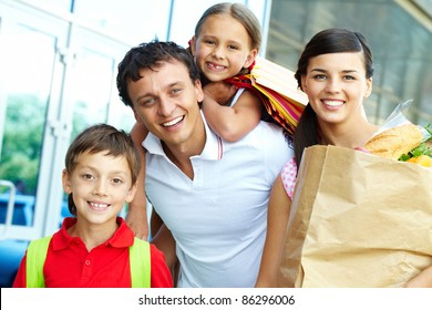 Couple with paperbags and their two children after shopping