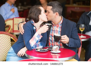 Couple in a Parisian street cafe, drinking coffee and kissing