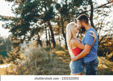 Couple in a park. Blonde in a pink t-shirt. Man with a beard