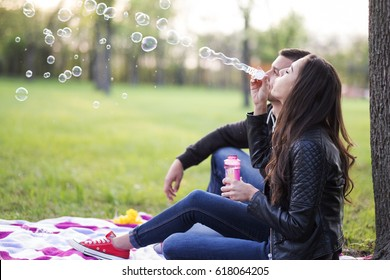 Couple in the park and blowing soap bubbles