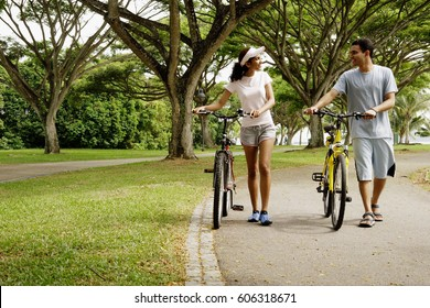 Couple in park, holding bicycles, walking