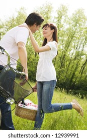 couple in park with holding picnic basket, kissing. Woman raises her leg