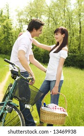 couple in park with holding picnic basket, hugging and smiling