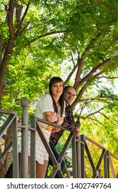 Couple in a park, they are on top of a bridge. Lifestyle concept, just married.