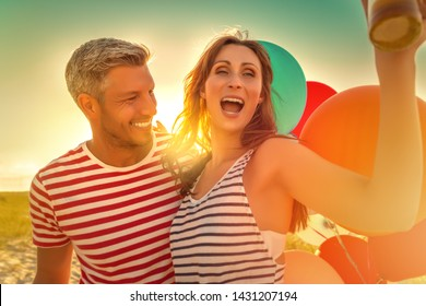 couple partying on the beach in sunset