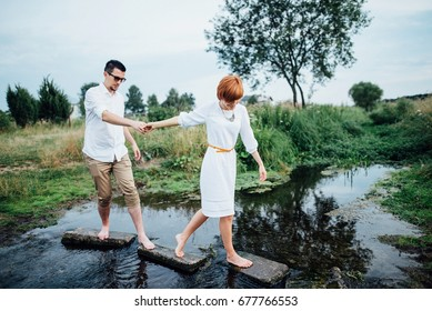 Couple pass through the river on the rocks
