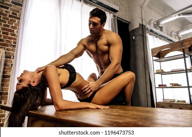 Couple.  Passion. Young sexy man and woman are going to have sex on the kitchen table. Man is bending a woman