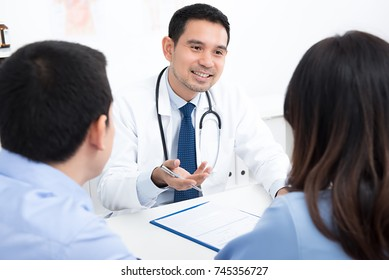 Couple patients consulting with handsome Asian male medical doctor in hospital room