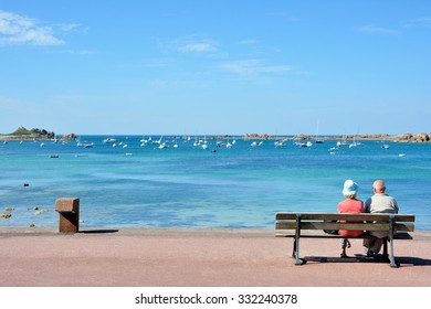 A couple of pensioners are waiting on a bench in front of the sea in Brittany