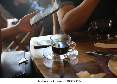 couple people with black hot coffee cup and cake on wood table in coffee shop, phone,Group of friends in shop on morning, lifestyle, retro color tone, discussion with friend  ,business