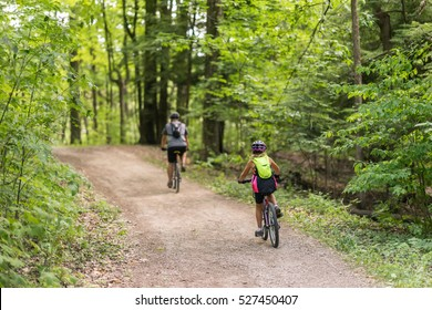 Couple of people cycling together in the woods down a dirt path on a beautiful summer day. Green canopy of trees above them. View from the back of people - full body.