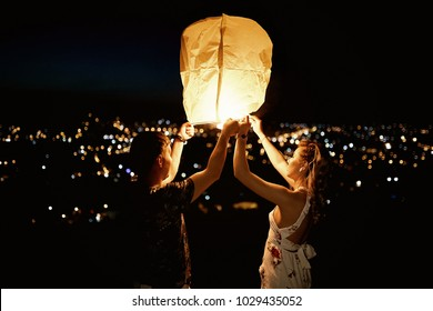 Couple of people in love launching a sky lantern in the evening. Summer night and city lights on the background. Romantic walk on a summer evening
