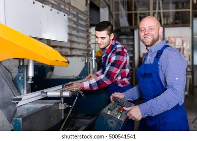 Couple of people near milling machine at factory