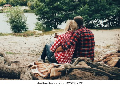 a couple of people in the plaid shirts sitting near the river on picnic and drinking tea