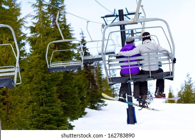 A couple of people ride the ski chair lift up the mountain together while sitting closely to each other having a fun time during a day of snowboarding in oregon.