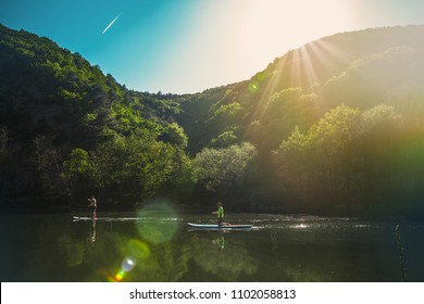 a couple of people slowly floating on the river on the sup-board, against the mountains and blue sky.