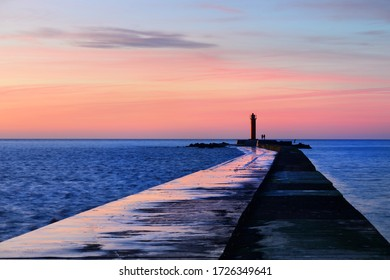 A couple of people standing near the orange lighthouse. Colorful sunset sky. Stunning cloudscape. Long exposure. National landmark, sightseeing, recreation theme. Baltic sea, Riga bay, Latvia