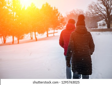 a couple of people walk in the winter Park