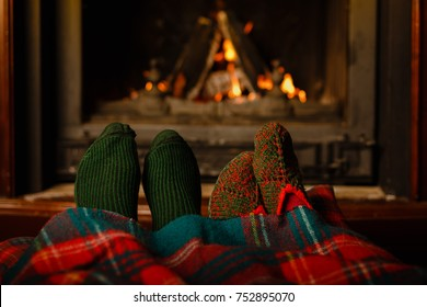 a couple of people warming his feet in front of the fireplace in the winter