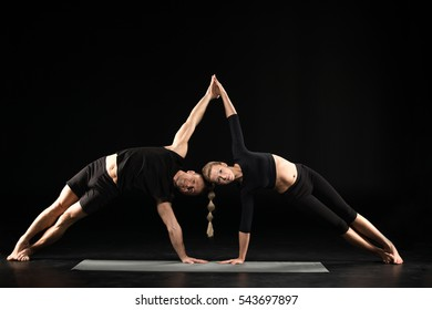 Couple performing acroyoga side plank on yoga mat isolated on black