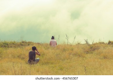 Couple photography on the grass field and enjoying view of nature.