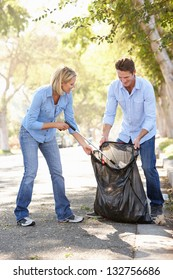 Couple Picking Up Litter In Suburban Street