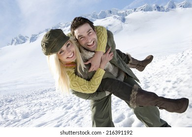 Couple piggy back riding in the snow