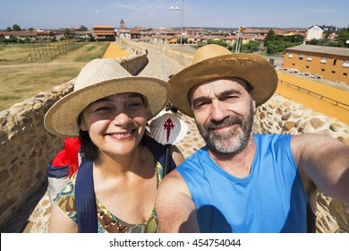 couple pilgrims selfie in Hospital de Orbigo bridge  , Way of St James,  Camino de  Santiago, to Compostela, Leon, Spain