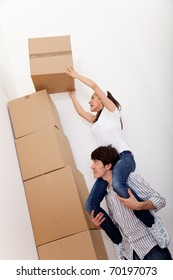 Couple piling cardboard boxes while packing for moving