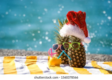 Couple of pineapples in Santa red hat and sunglasses on the sea beach. Romantic winter vacation for two. Happy Xmas and New Year holiday!