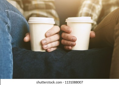 Couple in plaid shirts with two white paper cups of morning coffee