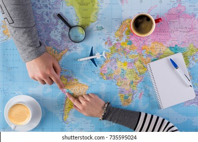 Couple planning airplane trip to Peru, point on map, taking notes in blank notebook, copy space