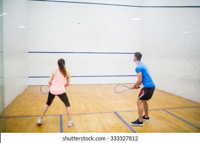 Couple play some squash together in the squash court
