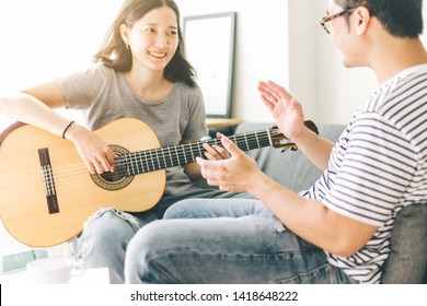 couple playing acoustic guitar,sing folk song together sitting on sofa at home.concept for happy moments of young lovers,family.music and art therapy for people with stress.asian man,women relax time