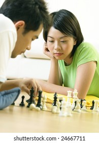 A couple playing chess on the floor