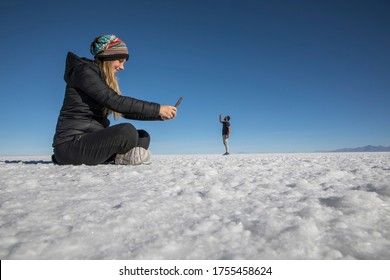 Couple playing in the desert salt flats, having fun with perspective